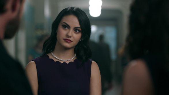 Veronica com suas pérolas no pescoço e um vestido vinho escuro