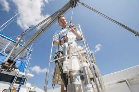 Dr. Christopher Gobler, of the Stony Brook University's School of Marine and Atmospheric Sciences, with a CTD device, an instrument that measures pH levels in depths of water, on board the Paumanok in Southampton, Aug. 20, 2014. (Credit: Gordon M. Grant)