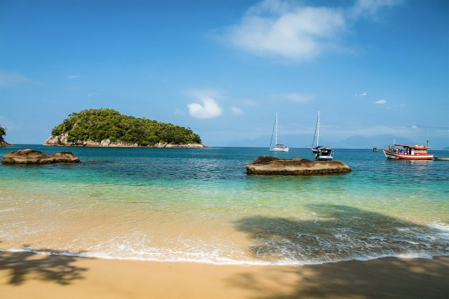 A beach on a sunny day with boats in the water in Ubatuba, Brazil.