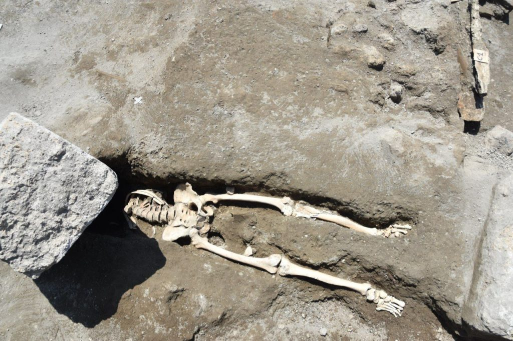 This skeleton of a man killed by a falling rock while fleeing the eruption of Vesuvius was recently discovered at the archaeological site of Pompeii. Photo courtesy of the Soprintendenza Archeologica di Pompei.