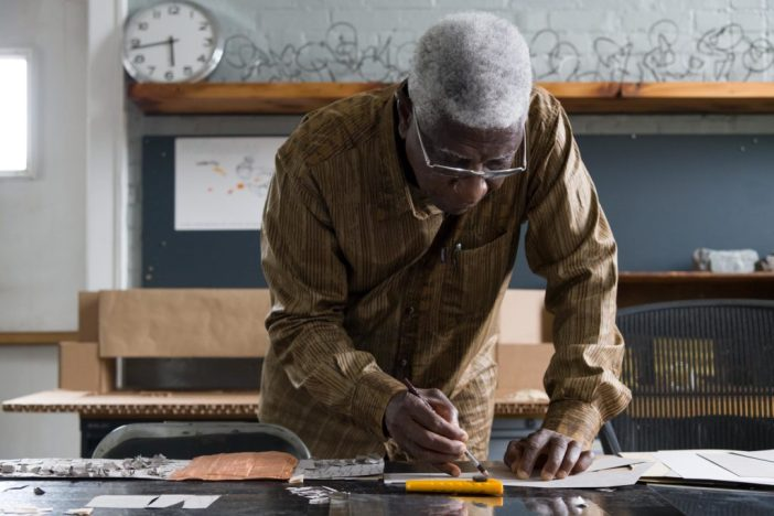 El Anatsui working on his installation for the 57th Carnegie International. Photo: Bryan Conley, courtesy of the Carnegie Museum of Art.