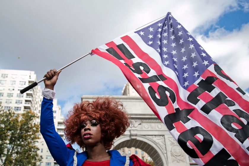 Honey Davenport with Shireen Liane's flag art at Michele Pred's We Vote Parade. Photo by Pontus Hook.