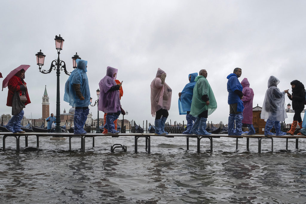 Tourists walk in the high water in Piazza San Marco on November 12, 2019 in Venice. Photo by Stefano Mazzola/Awakening/Getty Images.