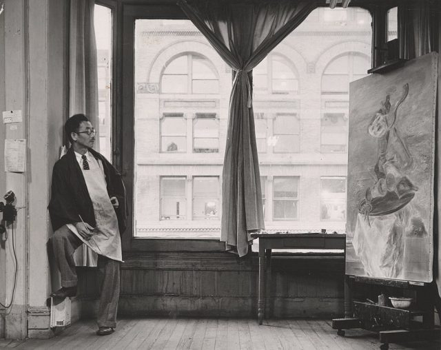 "Kuniyoshi working on his painting ""Upside Down Table and Mask"" in his studio near Union Square at 30 East Fourteenth Street in New York City. Photo by Max Yavno, courtesy the Archives of American Art."