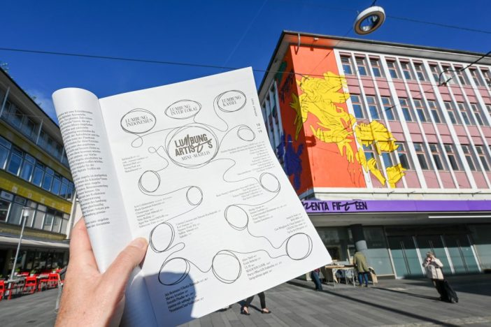 The October issue of the street newspaper <em>Asphalt</em>, opened to the page with the complete artist list of the exhibiting artists of documenta 15. (Photo by Uwe Zucchi/picture alliance via Getty Images)