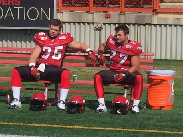 two football players on bench