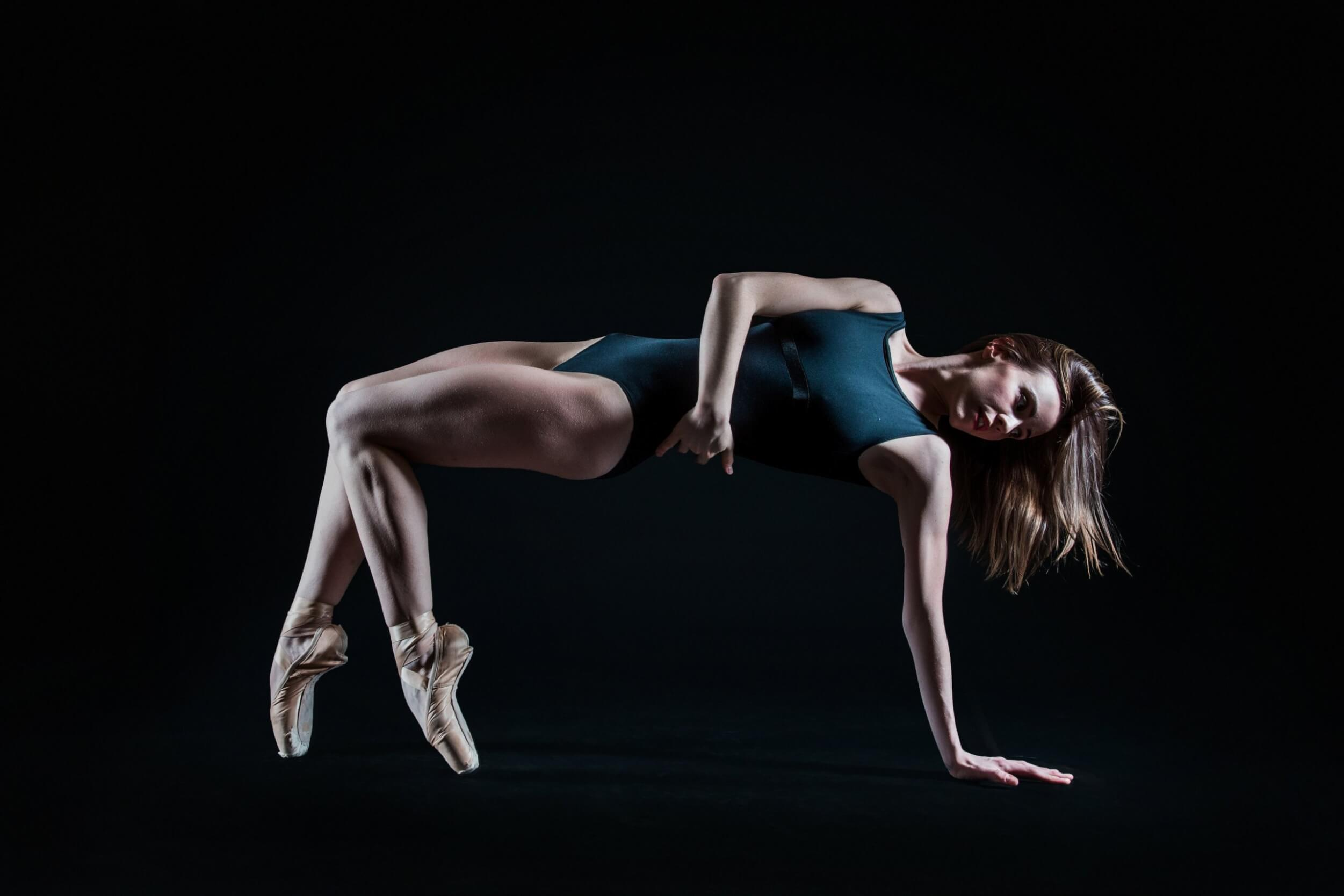 Kiera Keglowitsch in a turquoise bodysuit and ballet slippers posing in a ballet pose with two feet and on earm touching the ground