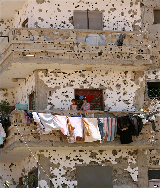 Palestinian girls stand on the balcony of the ruined house in Rafa, hit during Israels 22-day offensive against Gaza earlier this year, 2 July 2009 (Photo SAID KHATIB/AFP)