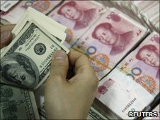 US dollar bills are counted as yuan notes are seen at a bank in Huaibei, China, file pic