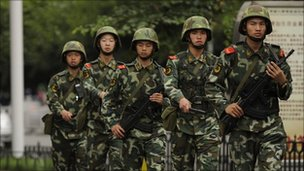 Chinese paramilitary policemen march past on a street in Urumqi on July 5, 2010