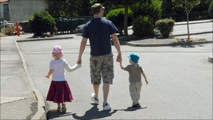A man walks with two children