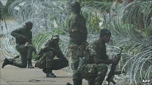 New Forces (FN) fighters adopt defensive combat positions outside the Hotel Golf in Abidjan, 13 December 2010