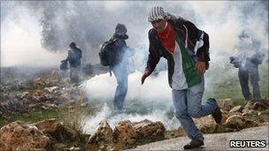 Protesters run from tear gas during a demonstration in Bilin, 31 December 2010