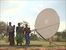 Zambian women walking past a satellite dish