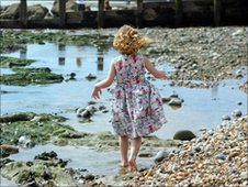 Little girl playing on a pebble beach