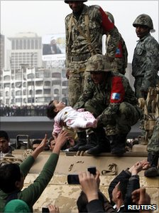 A protester reaches out as a soldier holds a child during a demonstration in Cairo, 29 January 2011.