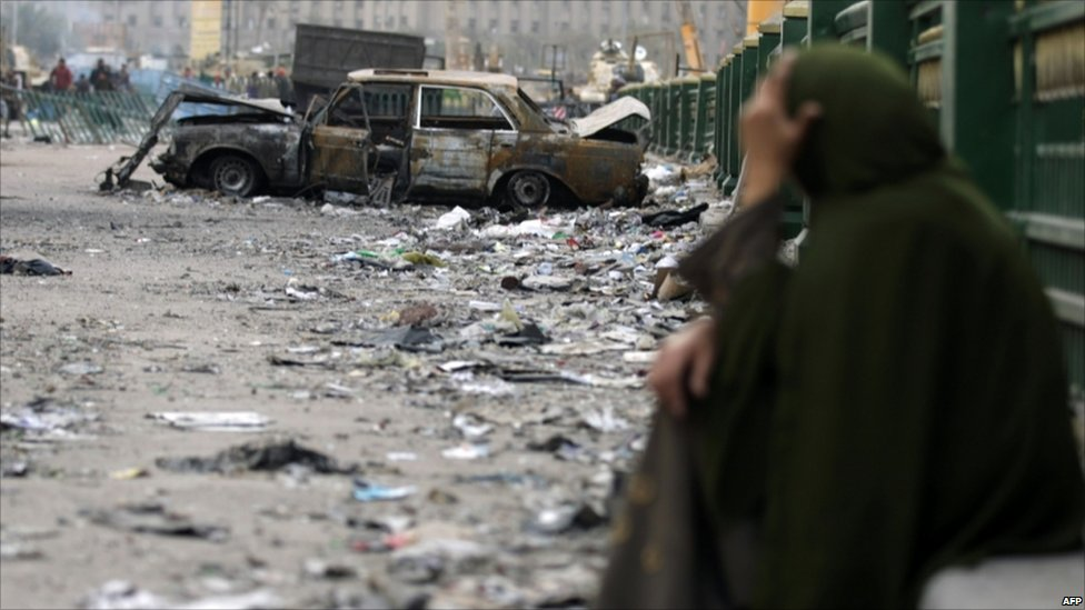 An Egyptian woman sits among the debris littering Cairo's Tahrir Square - 4 February 2011
