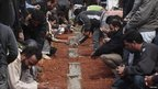 Mourners in Benghazi's cemetery bury the bodies of rebels killed in clashes with forces loyal to Libyan leader Muammar Gaddafi in Bin Jawad.