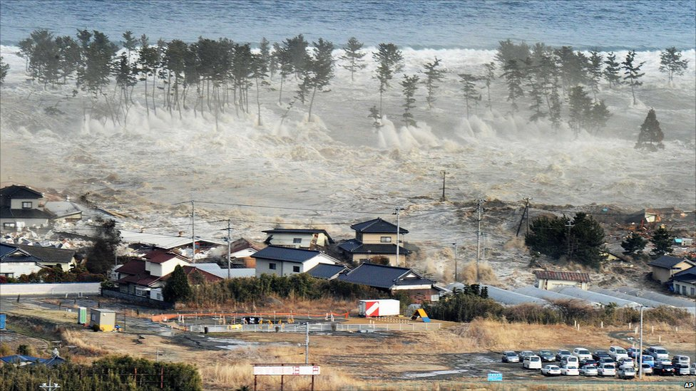 Waves of tsunami hit residences after a powerful earthquake in Natori