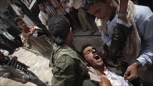 Injured Yemeni protester is carried in Sanaa (5 April 2011)