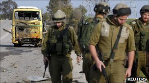 Israeli soldiers walk after investigating a bus that was damaged by an anti-tank missile fired from the Gaza Strip into southern Israel, April 7, 2011