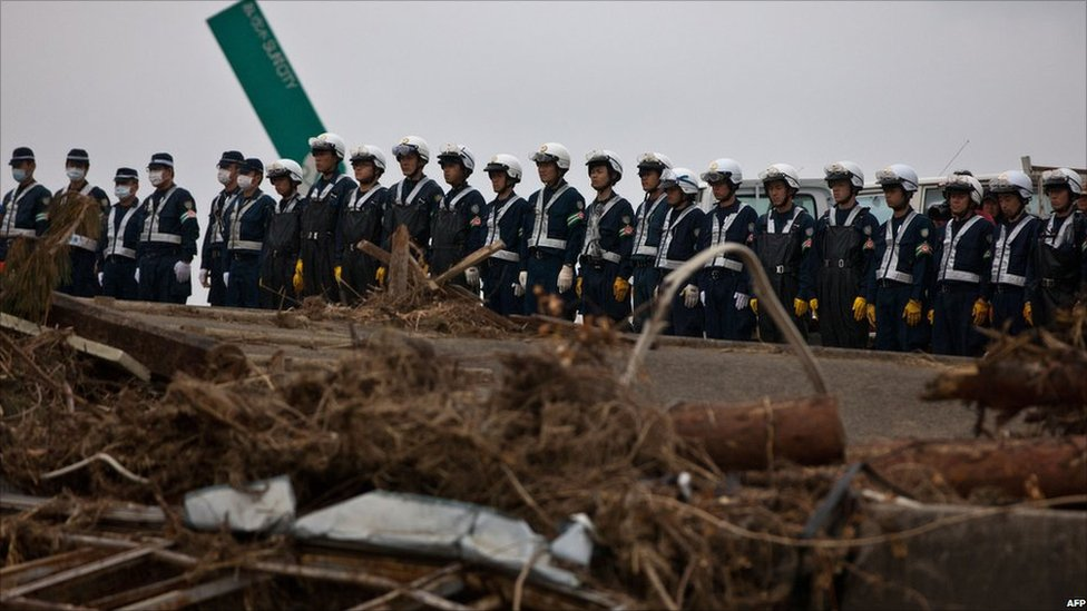 Japanese police observe a moment of silence in Ishinomaki, Miyagi, on 11 April 2011