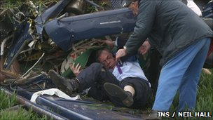 Nigel Farage being helped from the wreckage of the plane by a passer-by