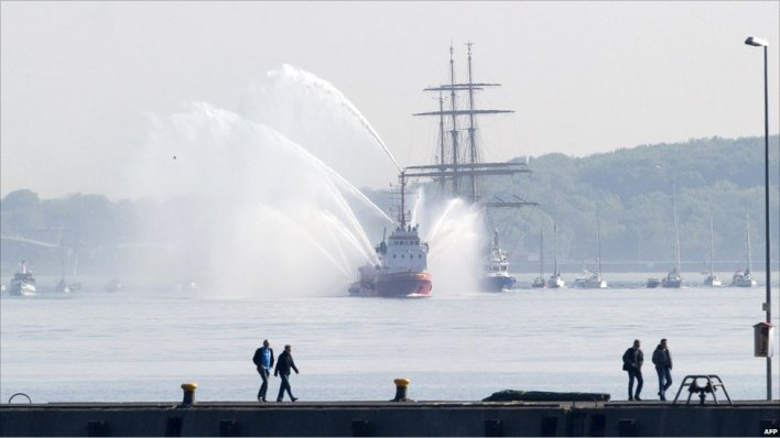 Boat spouts water onto the German navy tall ship Gorch Fock in Kiel harbour