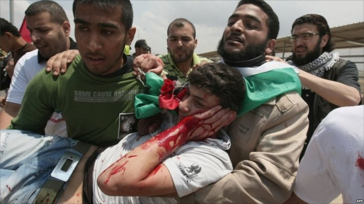 Injured man is carried away by Palestinians at Erez crossing, 15 May 2011