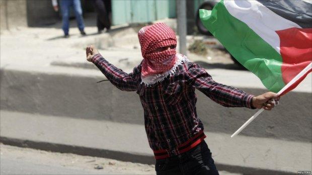 Palestinian throws stone during protest at Qalandiya checkpoint, near the West Bank city of Ramallah, 15 May 2011