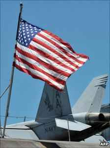 A US flag flutters next to a fighter jet on the deck of the US aircraft carrier Carl Vinzon