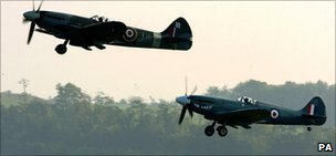 Two Spitfires fly in formation at an air show at Imperial War Museum Duxford