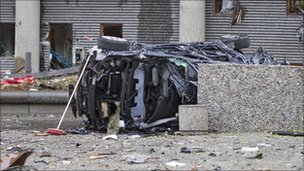 The wreckage of a car lies outside a building in the centre of Oslo