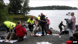 A wounded woman is brought ashore opposite Utoeya island (in the distance) after being rescued from a gunman who went on a killing rampage targeting participants in a Norwegian Labour Party youth organisation event on the island