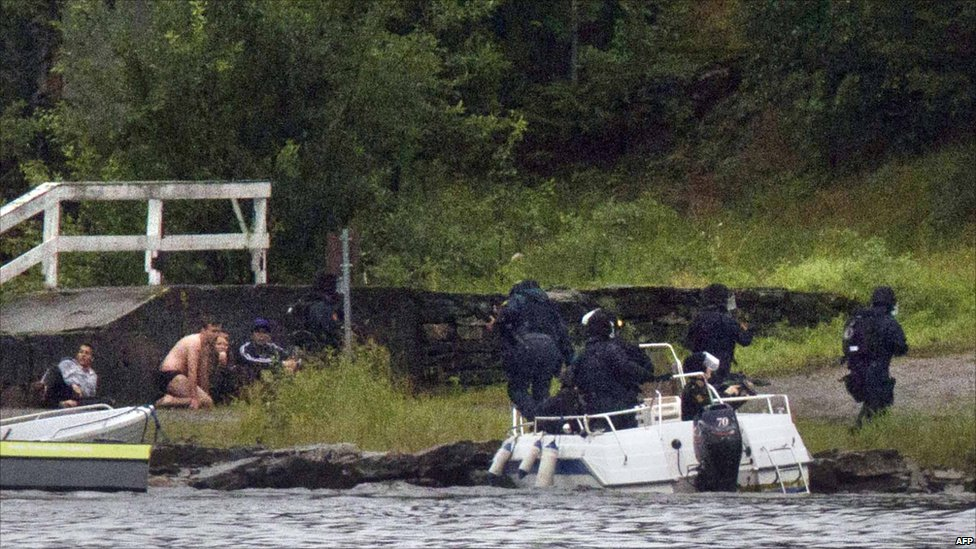 Armed police aim their weapons while people take cover after the shootings on Utoeya island, some 40km south-west of Oslo, 22 July 2011