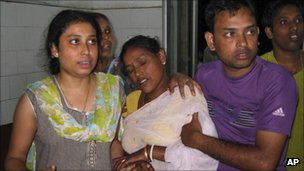 A woman, center who was injured in a building collapse that followed an earthquake is brought for treatment at a hospital in Siliguri, India, Sunday, Sept. 18, 2011