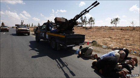 Anti-Gaddafi fighters pray near the front line outside Sirte. 28 Sept 2011