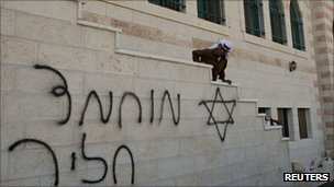 A Palestinian looks at Hebrew writing on the wall of a mosque in Qusra, near Nablus in September