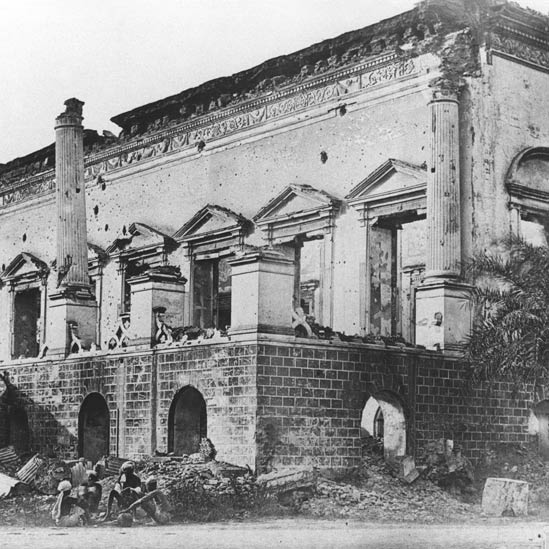 The Delhi Bank building wrecked during the Anglo-Indian War of 1857. The Delhi Bank, set up in 1847, owned by the Dyce Sombre family in Delhi, had other local businessmen as shareholders, was housed in this stately building. In May 1857, the manager of the bank, one Beresford, was killed by the rebels during the fighting. British forces took back the bank in September. | Image source & courtesy - bbc.co.uk | Click for larger image.