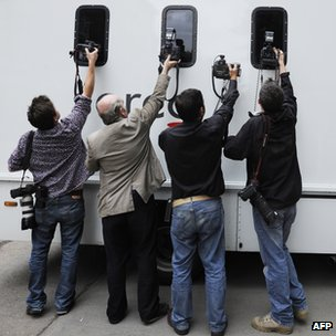 Press photographers take pictures of a prison van leaving the City of Westminster Magistrates Court in London