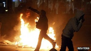 A protester throws stones at police in Bucharest. Photo: 15 January 2012