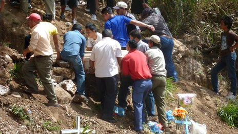 Ramon Varela's family and friends lowering the coffin into the ground