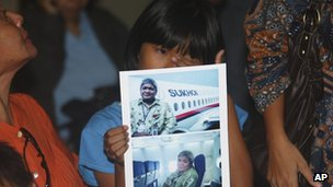 Tasya Kamagi, 10, holds pictures of his father Steven taken when he boarded the flight.