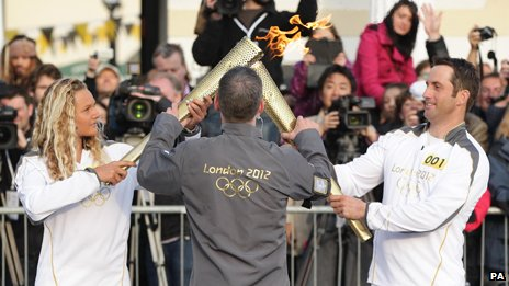 Second torchbearer Tassy Swallow receives the Olympic flame from Ben Ainslie