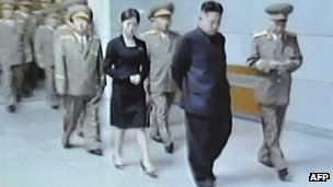 Screen grab taken from North Korean TV on July 9, 2012 shows an unidentified woman accompanying Kim Jong-Un (C) during his visit to Kumsusan Palace in Pyongyang on July 8, 2012