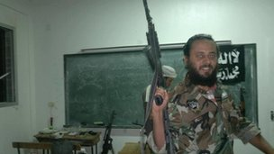 Abubakr holding gun in military fatigues in Syria