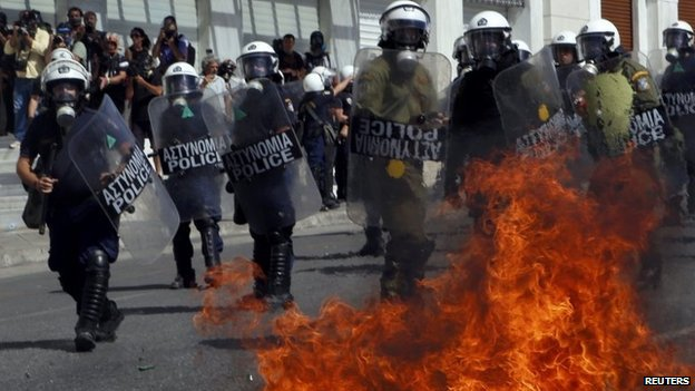 A petrol bomb explodes beside riot police officers near Syntagma square during a 24-hour labour strike in Athens, 26 September 2012
