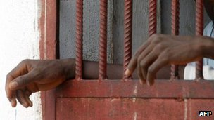 The hands of inmates seen through prison bars in Liberia (Archive shot)