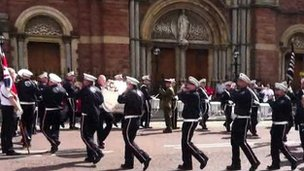 Band members were filmed playing contentious tunes while marching in circles outside the Catholic church