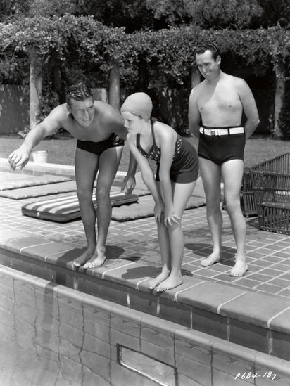 Harold Lloyd looks on as Buster Crabbe gives his daughter, Gloria, a swimming lesson at his Beverly Hills estate, Paramount Pictures, circa 1935